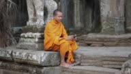 WS, PAN A Buddhist monk taps on the screen of a smartphone on the steps of an ancient temple in Angkor Wat / Siem Reap, Cambodia