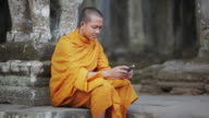 MS A Buddhist monk taps on the screen of a smartphone on the steps of an ancient temple in Angkor Wat / Siem Reap, Cambodia