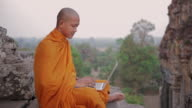 MS, PAN A Buddhist monk types on a laptop computer and pauses to think, on top of an ancient temple in Angkor Wat / Siem Reap, Cambodia