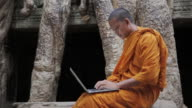 MS A Buddhist monk types on a laptop computer next to an old tree and ancient temple in Angkor Wat / Siem Reap, Cambodia