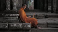 WS A Buddhist monk uses a laptop computer on the steps of an ancient temple in Angkor Wat / Siem Reap, Cambodia