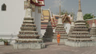 MS PAN buddhist monk walking along pagodas and temples in Wat Pho; enters frame right, exits frame left, RED R3D 4K