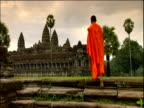 Buddhist monk wearing orange robes walks up steps towards Angkor Wat temple Cambodia