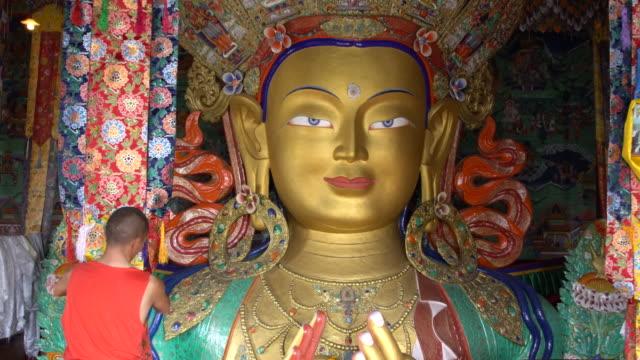 Buddhist monk working close to the statue of Maitreya inside Thiksay Monastery, Ladakh, India