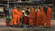 Buddhist monks buying at food stall and laugh