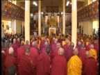 Buddhist monks gather in a temple with the Dalai Lama