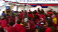 Buddhist monks sit in tent watching television, Tibet Available in HD.