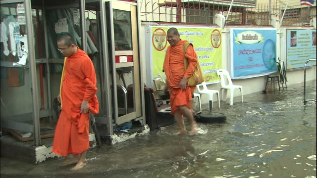 Buddhist Monks wade through flood water as they move past stores