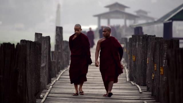 Buddhist Monks walk across a Bridge at Sunrise 2