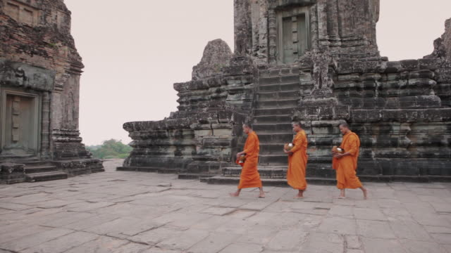 WS, PAN Buddhist monks walk across a temple with alms bowls, high above the jungle in Angkor Wat, on their way to collect offerings / Siem Reap, Cambodia