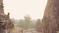 WS, PAN Buddhist monks walk along the top of an ancient temple high above the forest in Angkor Wat at sunrise / Siem Reap, Cambodia