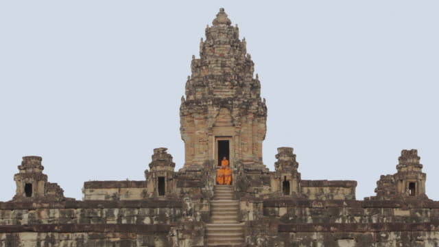 LS Buddhist monks walk down the steps of an ancient temple in Angkor Wat carrying alms bowls to collect offerings / Siem Reap, Cambodia