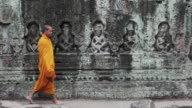 MS Buddhist monks walk past an intricately carved stone wall in an ancient Angkor Wat temple / Siem Reap, Cambodia