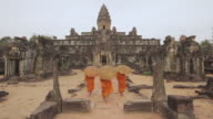 WS Buddhist monks walk through the courtyard of an ancient temple in Angkor Wat carrying parasols / Siem Reap, Cambodia