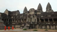 WS Buddhist monks walking in front of ancient temple / Angkor Wat, Siem Reap, Cambodia