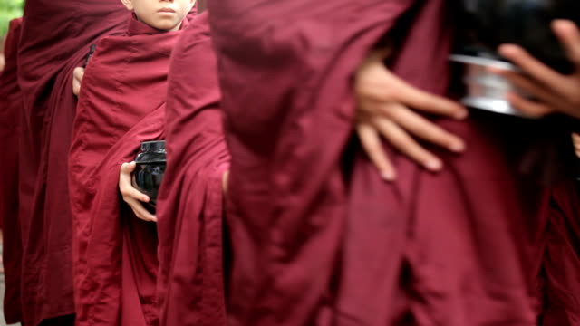 Buddhist novices walk to collect alms and offerings in Mandalay, Myanmar