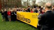 Liberal Democrats reaction Danny Alexander MP and other Liberal Democrats holding up banner '£800 Tax Cut Delivered' / Deputy Prime Minister Nick...