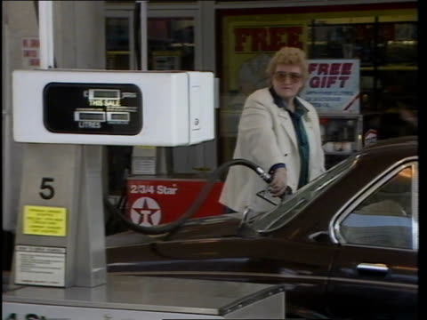 London MS Petrol prices sign showing price of 1749 per gallon of 4 star MS Texaco petrol station BV SIDE woman filling tank MS Woman filling tank...