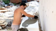 Builder covers the polystyrene with construction glue.