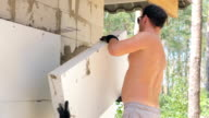 Builder covers the wall with polystyrene.
