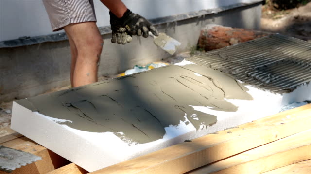 Bouwer toebrengt lijm op polystyreen te bouwen.