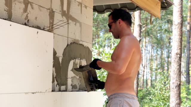 Bouwer zet de bouw lijm op de muur.