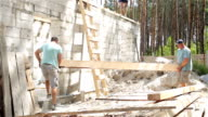 Builders carry a wooden beam into the house.