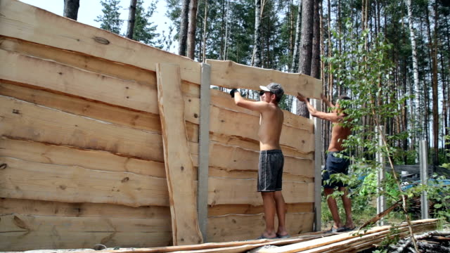 Builders make a wooden fence.