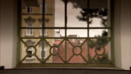 Buildings and rooftops can be seen through iron railings. Available in HD.