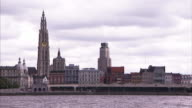 Buildings line a river in Antwerp.