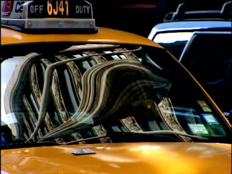 Buildings reflected in windscreen of yellow taxi Manhattan
