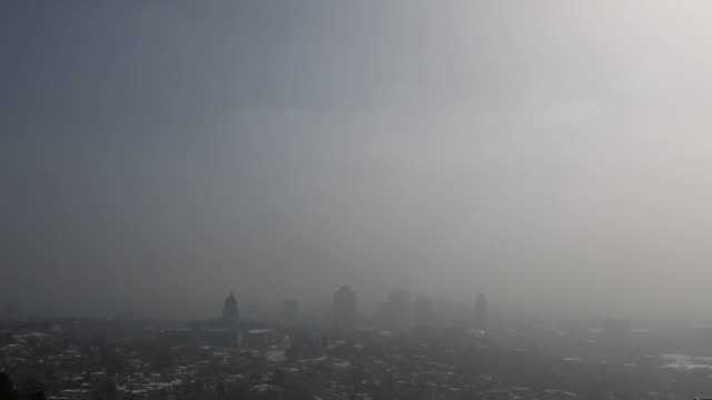 Buildings stand past smog from a winter temperature inversion in Salt Lake City Utah US on Wednesday Feb 10 2016 With warmer air above and cooler in...