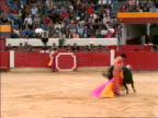 Bull charging matador + running through cape as matador moves out of way / Bogota, Colombia