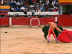 Bull with banderillas in neck circling + charging matador with red cape / Bogota, Colombia