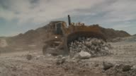 A bulldozer clears rocks and rubble at a quarry site. Available in HD.