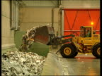 Bulldozer dumping waste paper into vast pit paper falling into container