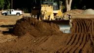 Bulldozer bewegen Erde in Richtung Betrachter
