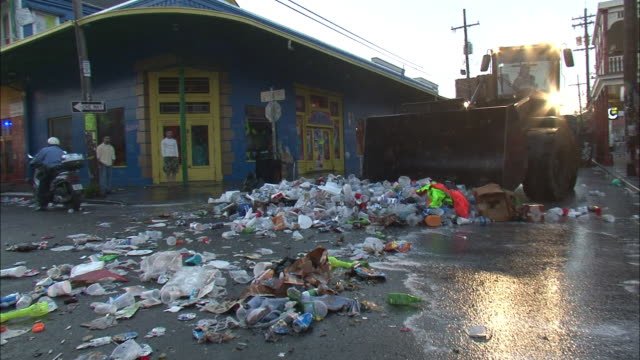 A bulldozer scoops all kinds of trash off a street in New Orleans.