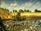 Bulldozers flattening rubbish on vast landfill site below English countryside