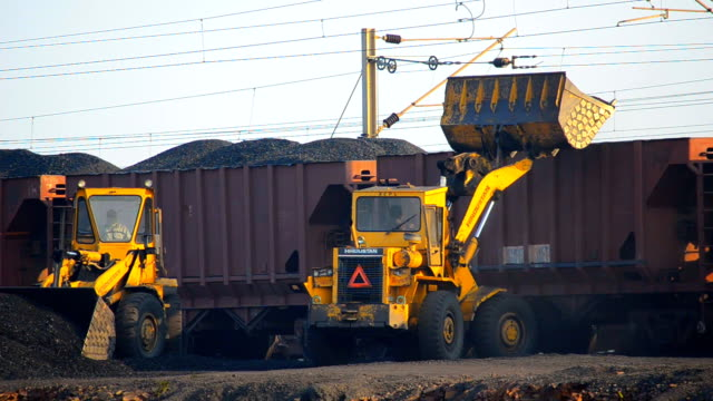 Bulldozers loading coal in train wagon