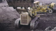 1969 MONTAGE Bulldozers removing black shale waste for disposal from Chislet colliery / Ramsgate, Kent, England
