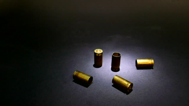Bullet casings dropping on street night crime scene