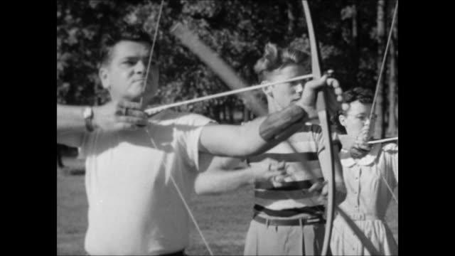 Bullseye archery target on outdoor archery range Line of people men woman standing yards from targets VS People pulling back bow strings aiming arrow...