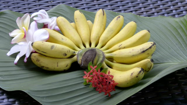 A bunch of finger bananas decorated with frangipani flowers