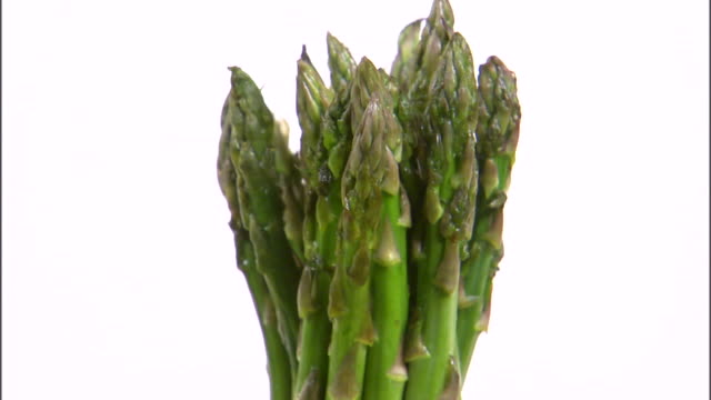 MS ZI CU Bundle of asparagus rotating against white background / Orem, Utah, USA