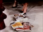 1956 CU Bundles of magazines landing at woman's feet next to fire plug / USA