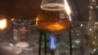 A Bunsen burner heats liquid in a glass flask. Available in HD.