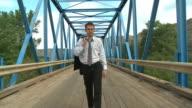 Bunsiness man walks across bridge