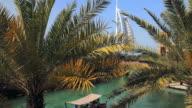 WS Burj Al Arab hotel from souk Madinat, palm leaves in foreground / Dubai, United Arab Emirates