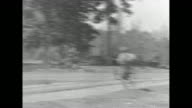 Burmese soldiers stand at attention / VS soldiers running across field and approaching a house / men running with guns indoors / a prisoner tied with...